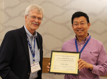 Dr. Haibo Zhou receives the 2019 NISS Distinguished Alumni Award from Jim Rosenberger.