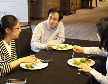 Young researchers meet with mentors about their writing over lunch.